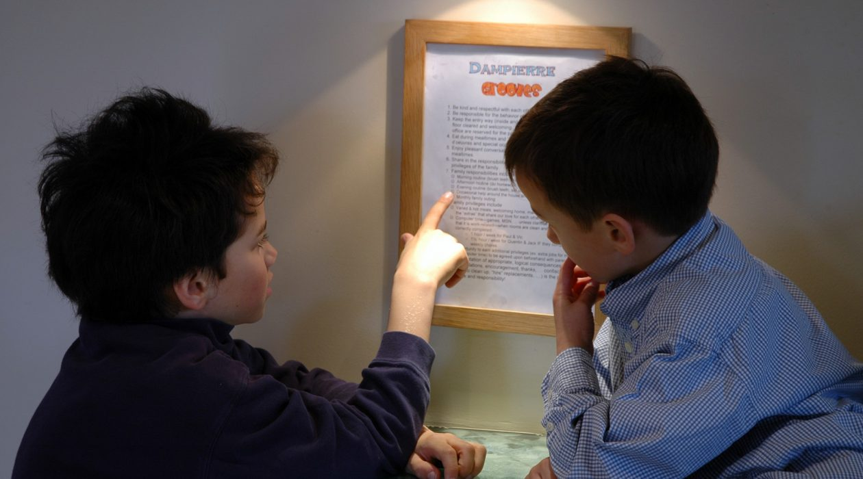 Older brother reading house rules to young boy