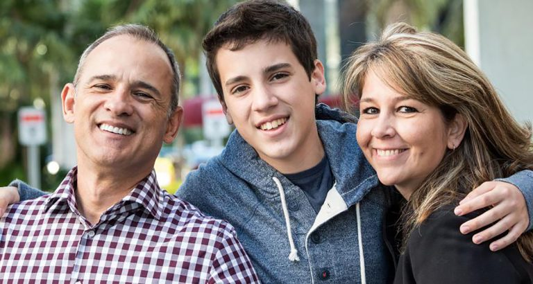 smiling teenager with parents