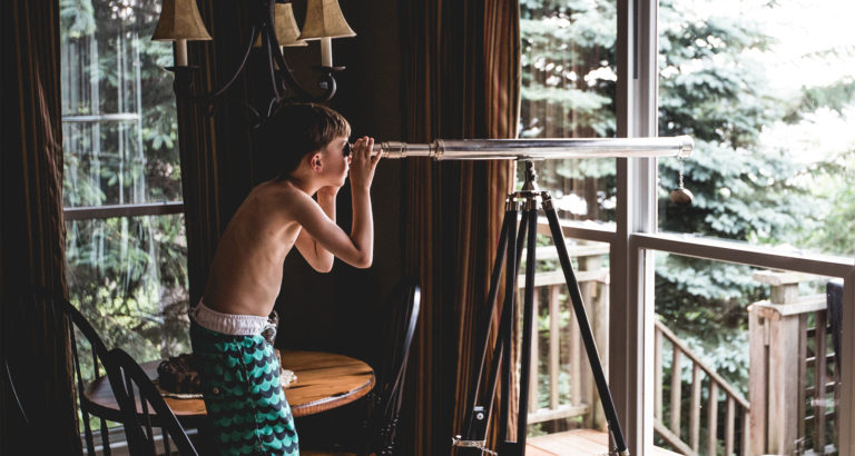 Boy looking through telescope. Searching Focus word!
